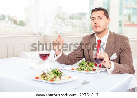 Attractive successful man is meeting his business partner. He is looking forward with concentration. The man is sitting at the table and gesturing - stock photo