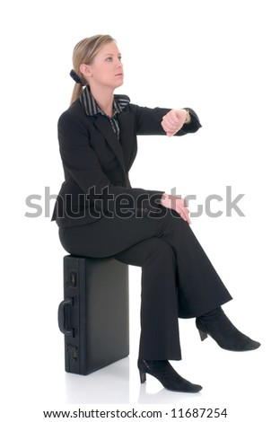 Attractive successful young businesswoman  sitting on briefcase, suitcase, awaiting appointment.  studio shot.