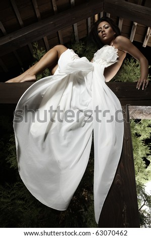 Attractive suntanned girl in white dress poses on a wooden beam. - stock photo