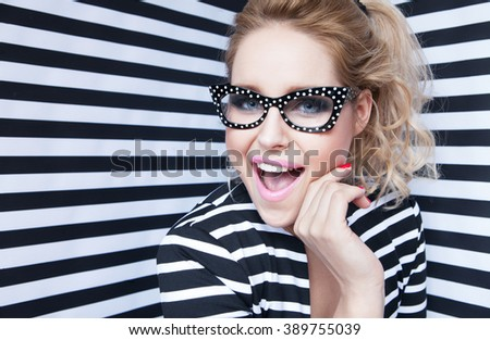 Attractive surprised young blonde woman wearing glasses on stripy background, beauty and fashion concept  - stock photo