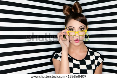 Attractive surprised young woman wearing glasses on checkered background, beauty and fashion concept  - stock photo