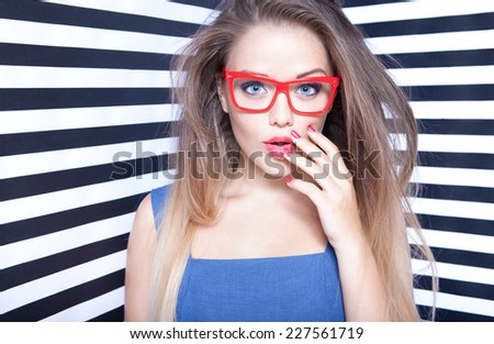 Attractive surprised young woman wearing glasses on stripy background, beauty and fashion concept - stock photo