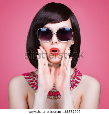Attractive surprised young woman wearing sunglasses