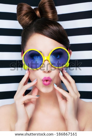 Attractive surprised young woman wearing sunglasses on striped background, beauty and fashion concept  - stock photo
