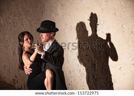 Attractive tango dancers under spotlight in urban setting - stock photo