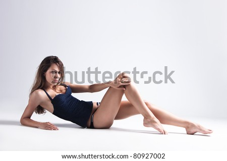 attractive tanned brunette in blue underwear lie on floor, full body shot, small amount of grain added, studio shot - stock photo