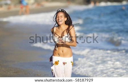 Attractive tanned girl running along the beach - stock photo
