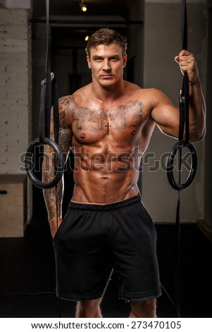 Attractive tattooed man with naked torso in a gym - stock photo