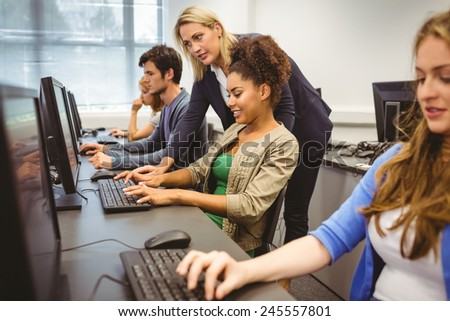Attractive teacher helping her student in computer class at the university - stock photo