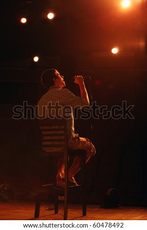 attractive teen boy on stage with microphone
