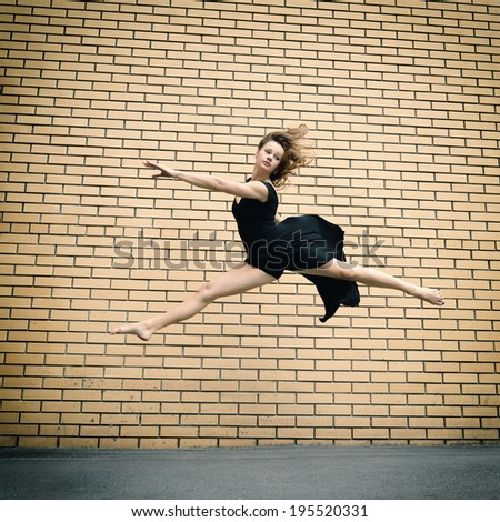 Attractive teen girl dancing outdoor against brkics wall. Toned. - stock photo