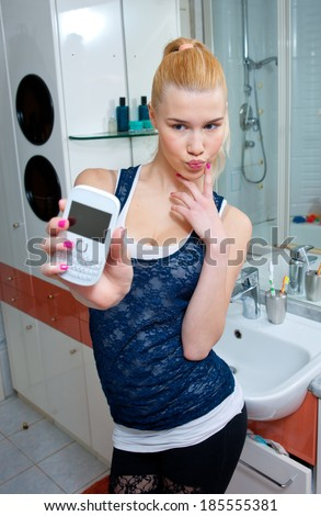 attractive teen girl making selfie with mobile phone in her bathroom - stock photo