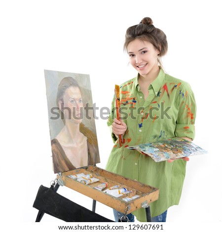 attractive teen girl painter drawing portrait with oil paints, professional painter at work over white background - stock photo