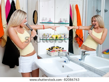attractive teen girl singing in the bathroom - stock photo