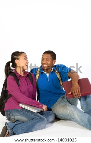Attractive teenage age couple wearing backpacks and holding books, looking at each other with big smiles. - stock photo