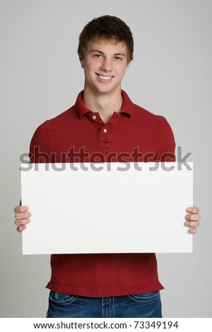 Attractive teenage boy holding a blank sign isolated on white background - stock photo