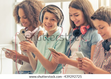 Attractive teenage boy in headphones is using a smartphone, looking at camera and smiling while sitting among other teenagers - stock photo