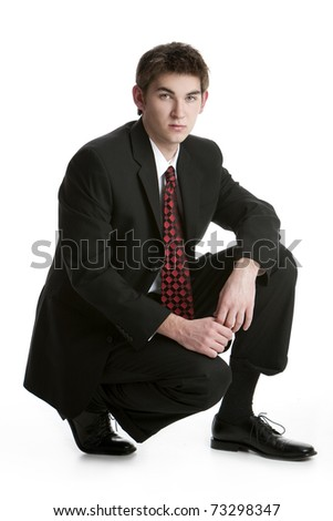 Attractive teenage boy kneeling in a suit isolated on white background - stock photo