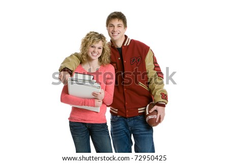 Attractive teenage couple holding books and football with white background