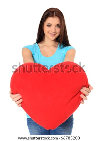 Attractive teenage girl holding red heart-shaped pillow. All on white background. - stock photo
