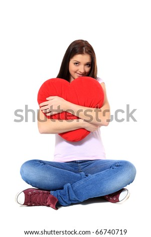 Attractive teenage girl hugging red heart-shaped pillow. All on white background. - stock photo