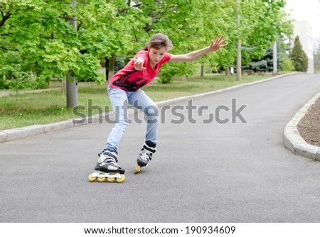 Attractive teenage girl roller skating on roller blades on a tarred rural road rounding a bend at speed with her arms flying - stock photo