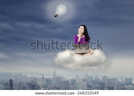 Attractive teenage girl sitting on the cloud while using a laptop and looking up at a lightbulb - stock photo