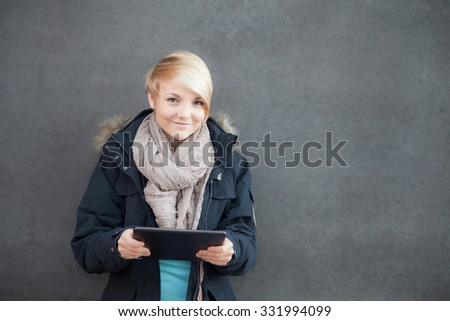 Attractive teenage girl using tablet device