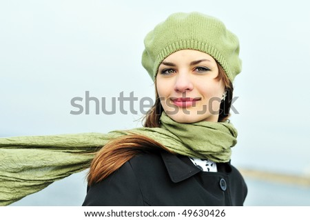 attractive teenage girl wearing beret standing outdoors in windy day - stock photo