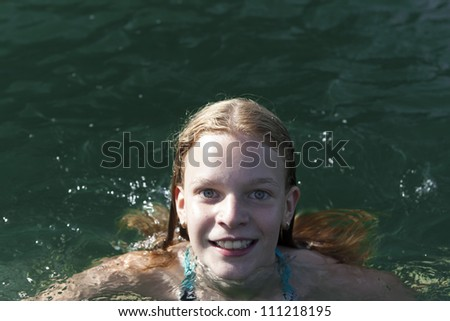 Attractive teenage girl with a lovely merry smile swimming in a lake with sunlight on the water and copyspace