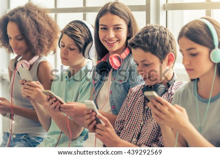 Attractive teenage girl with headphones is using a smartphone, looking at camera and smiling while sitting among other teenagers - stock photo