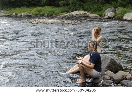 Attractive teenage girls enjoy playing around river.