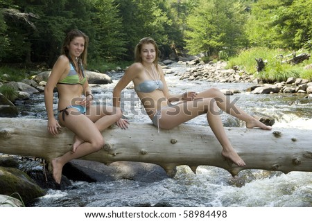 Attractive teenage girls ride a log over the mountain river. - stock photo