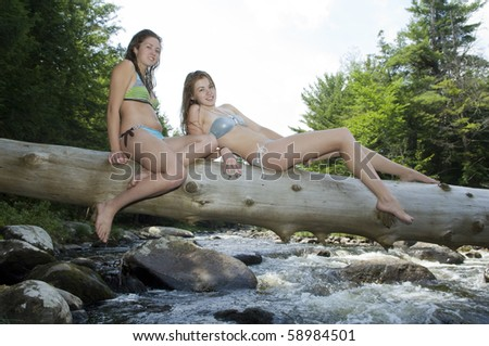 Attractive teenage girls ride a log over the mountain river.