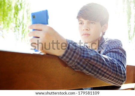 Attractive teenager boy sitting down on a wooden bench in a park holding and using a smartphone against a sunny sky with sun rays and flare filtering in, outdoors. Technology lifestyle. - stock photo