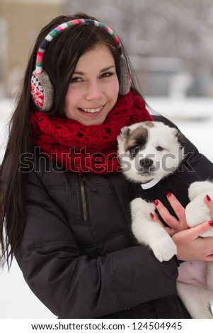 Attractive teenager girl in earplugs on walk in a bright winter day