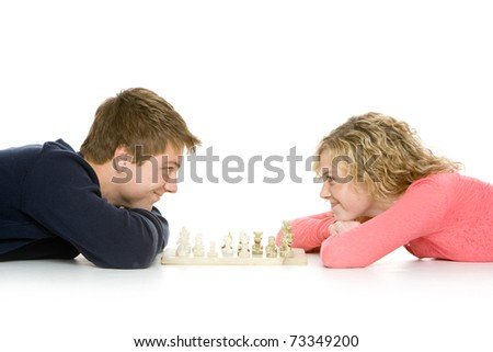 Attractive teenagers lying down using playing chess, isolated on white - stock photo