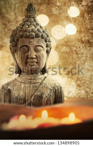 attractive textured picture of a Buddha figure with floating candles in a stone bowl