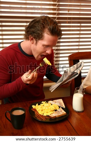 Attractive thirty something man eating breakfast and reading paper.