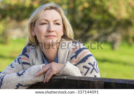 Attractive thoughtful middle aged woman leaning resting on fence in the countryside - stock photo