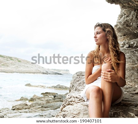 Attractive thoughtful woman relaxing on a coastal textured rock mountain wrapped in a white sarong, sunbathing and relaxing during a summer holiday trip by the sea. Beauty and health lifestyle. - stock photo