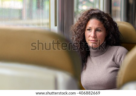 Attractive thoughtful woman travelling by train viewed between two seats sitting staring ahead with a serious, contemplative expression - stock photo