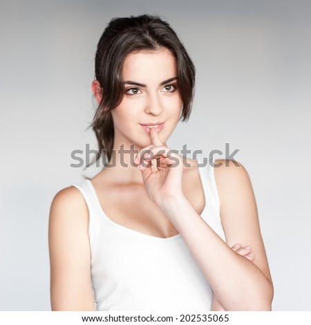 attractive thoughtful young casual caucasian brunette  woman in white singlet looking away over gray background - stock photo