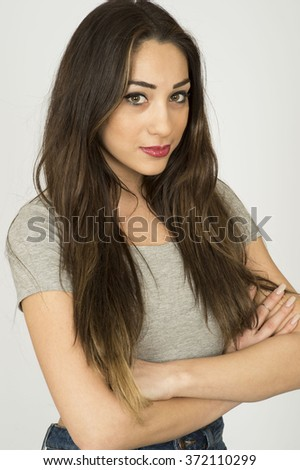 Attractive Thoughtful Young Dark Haired Woman Sitting With Her Arms Folded Looking At The Camera Shot Against A Plain White Background - stock photo
