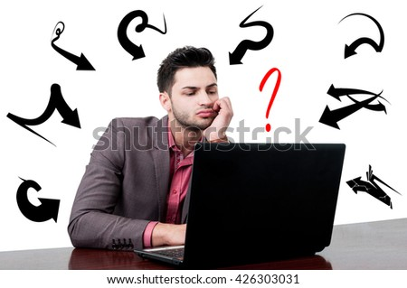 Attractive tired businessman working on his computer and taking a decision with arrows and question mark above his head - stock photo