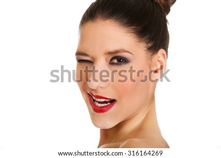 Attractive topless woman with dark make up blinks eye. - stock photo