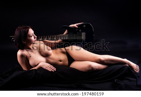 Attractive topless woman with electric guitar. Studio shot over black background - stock photo