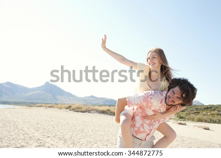 Attractive tourist couple on holiday, with man carrying girl in piggyback against sunny blue sky, joyful outdoors space. Romance and dynamic honeymoon fun lifestyle, summer exterior. - stock photo