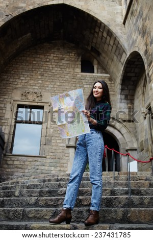 Attractive tourist girl on vacation with a map in antique gothic city, charming tourist woman studying a map standing in gothic quarter, young female traveler searching right direction on city map - stock photo