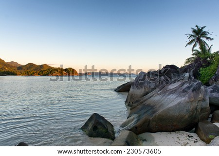 Attractive Tranquil OceansideView with Large Rocks and Palm Trees in Port Launay, Seychelles. Captured with Mountains Afar During Sunrise. - stock photo